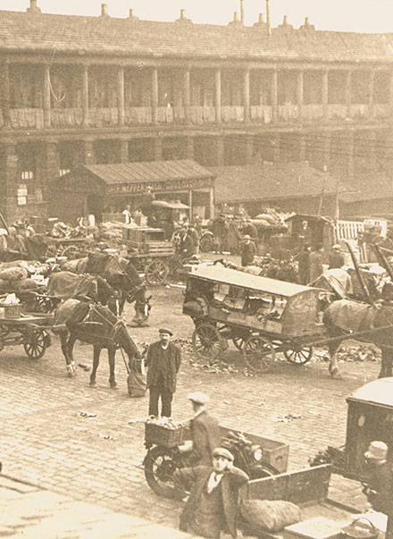 Historical, sepia image of the courtyard, populated by horse drawn carts.