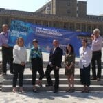 The piece hall team stand infront of a banner for the National Lottery Awards of 2018.