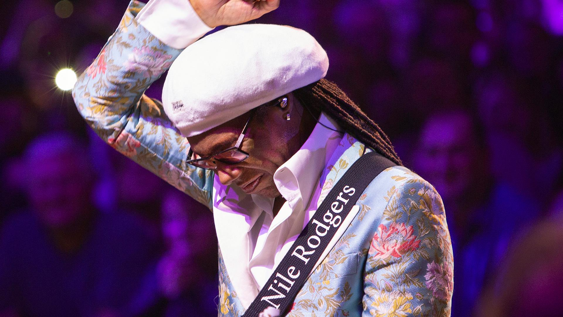 Nile Rodgers in floral blue blazer and white beret, lifts arm above head when performing for crowd.