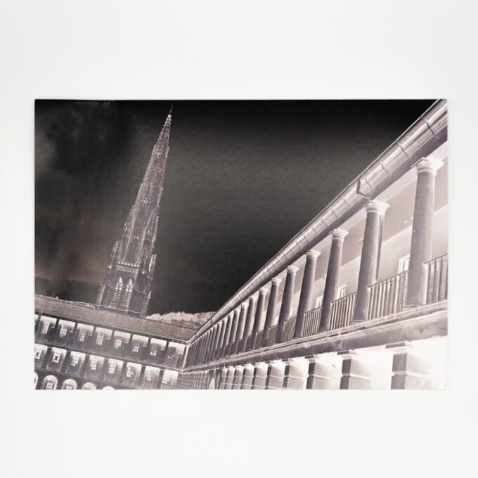 negative grey-scale image of courtyard and church spire.