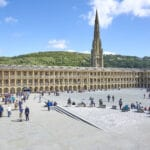 The piece hall courtyard, populated by visitors on a sunny day.