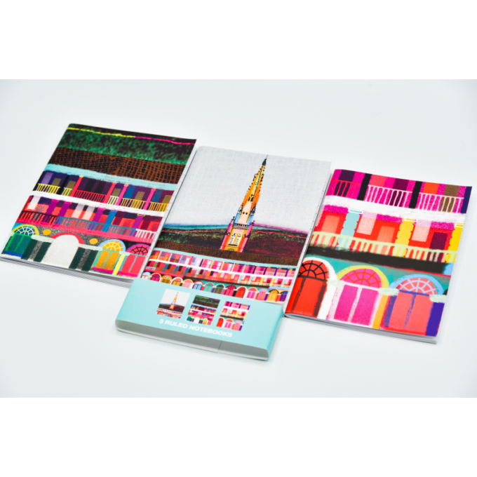 A 3 pack of notebooks, depicting a multicoloured piece hall on the cover.