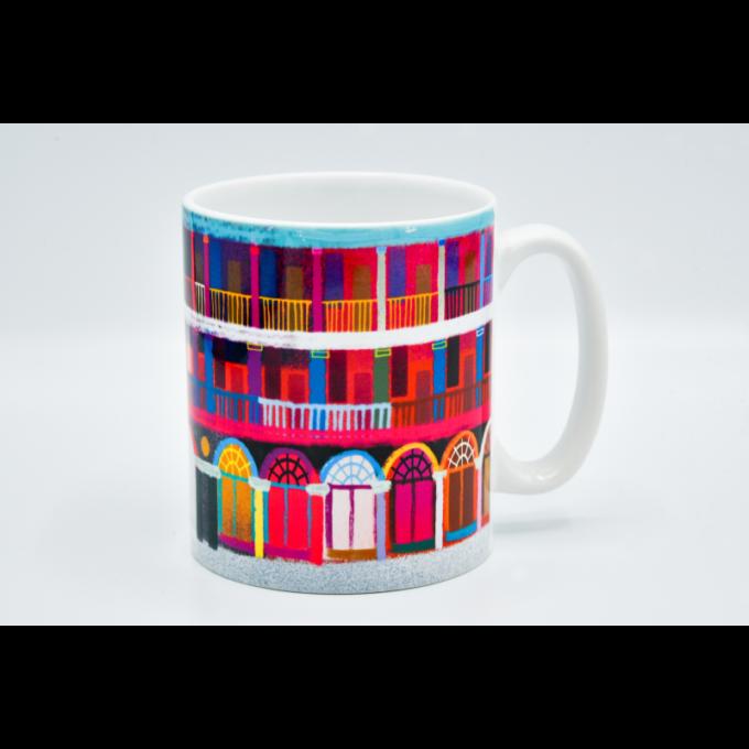 A multicoloured piece hall print around a ceramic mug.