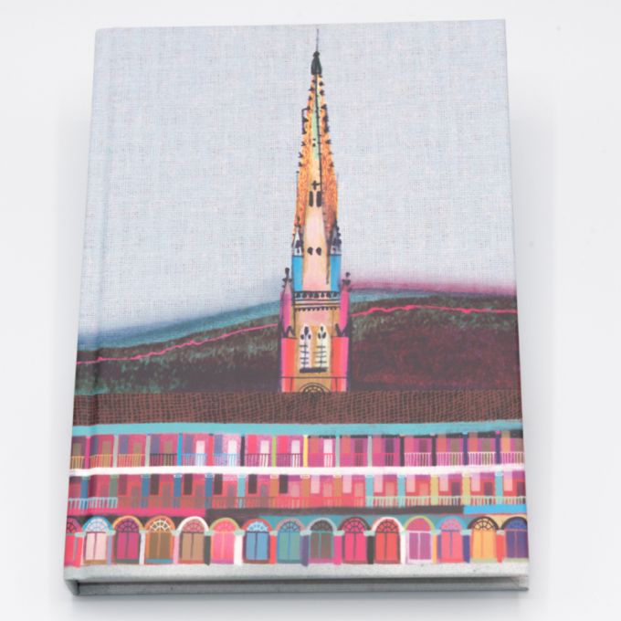 A multicoloured piece hall sits on the cover of a hardback notebook.