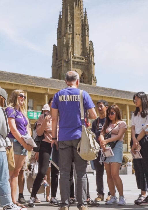 A group of people gather to listen to a man wearing a Volunteer shirt.