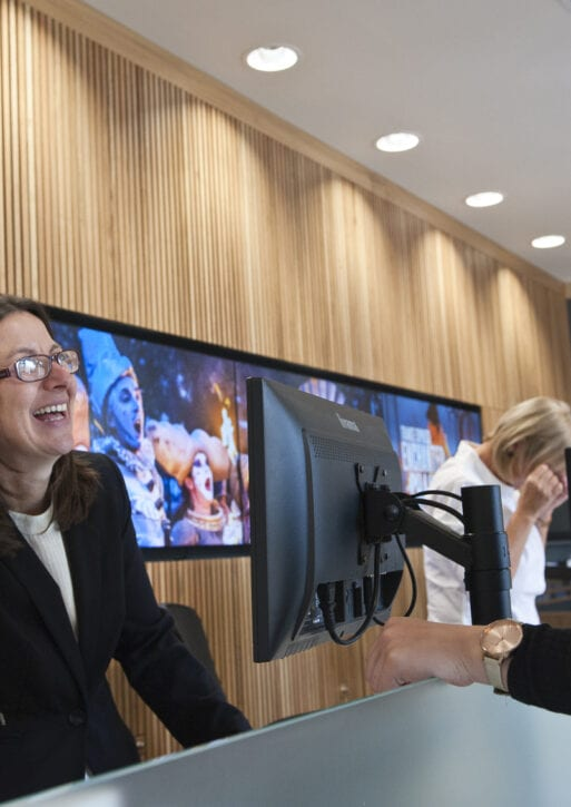 A woman laughs with the receptionist at the front desk.