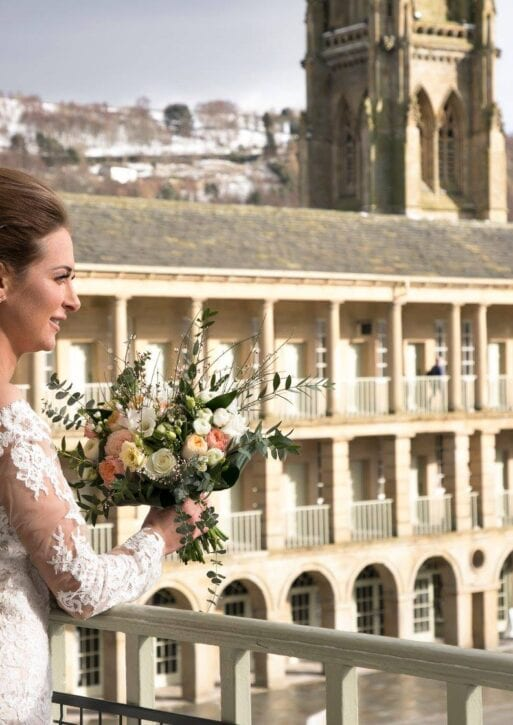 A bride looks out onto the courtyard of the piece hall, holding a bouquet.